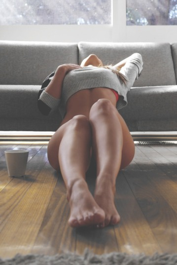 girl sat on floor leaning back against grey sofa escort barcelona greay crop top